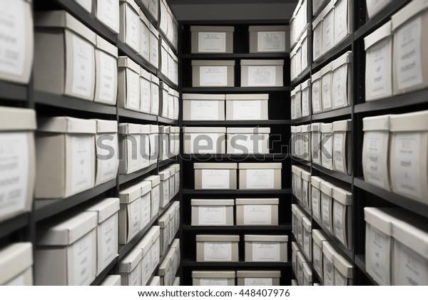 Хранение архива депозитария комната черные полки с белыми офисными коробками карты картотека доказательств.