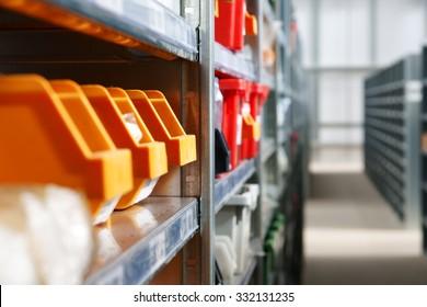 Storage bins and racks for storing parts and components in a warehouse shot with shallow focus