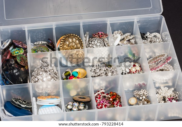 a storage box of buttons used to create jewelry