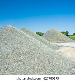 Storage of bulk materials; Piles of bright fine gravel against clear blue sky; Supplier of aggregates and construction materials; Gravel plant