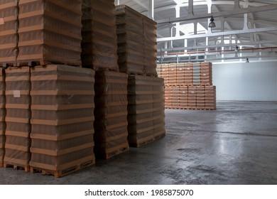 Lagerung und Beförderung in der industriellen Lebensmittelindustrie. Klarglasflaschen für alkoholische oder alkoholfreie Getränke und Konservengläser, die auf Paletten für Gabelstapler gestapelt sind.