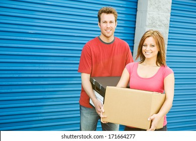 Storage: Couple Carrying Boxes To Storage Unit