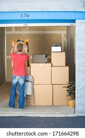 Storage: Man Stacking Boxes and Things In Storage