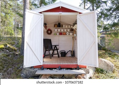 Storage shed filled with garden tools. Shovels, rake, pots, water pitcher and all you need for gardening.
