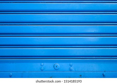 Storage shutter roller steel door with blue stripes textured background and hole key lock below for security to entrance industrial warehouse factory