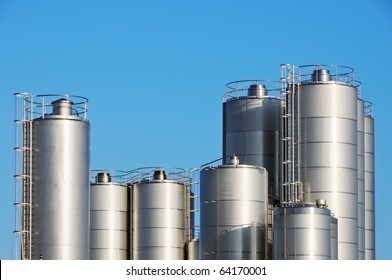 Storage tanks of dairy plant against blue sky.