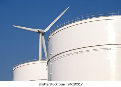 Storage tanks in front of a tall windmill