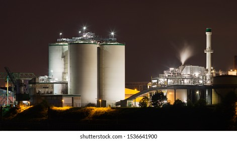 Storage tanks and other parts of a chemical plant at night.