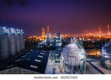 Storage tanks in warehouse with glitter lighting of petrochemical estate on background