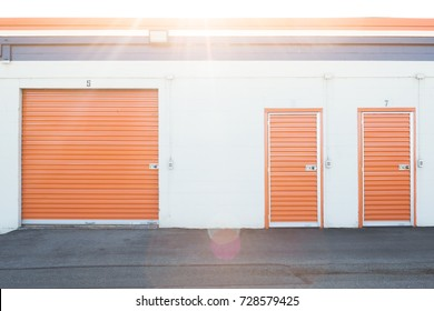 Storage unites with orange doors and white walls. Early morning sunrise.