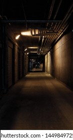 Storage units with metal shutters in a dark basement passage
