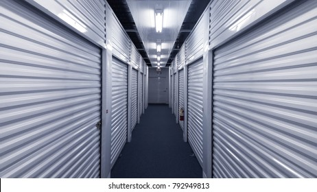 Storage units on a blue carpeted hallway.