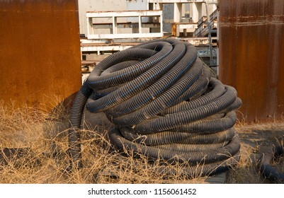 The storage yard of an industrial plant is filled with rusted and discarded material that is no longer needed.