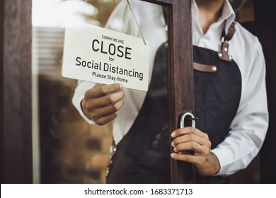 Store owner turning close sign broad through the door glass for social distancing prevent corona virus outbreak.