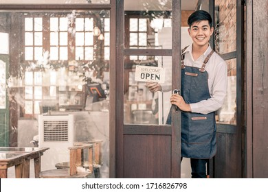 Store owner turning open sign broad through the door glass and ready to service. - Shutterstock ID 1716826798