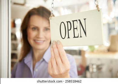 Store Owner Turning Open Sign In Shop Doorway