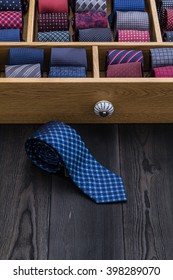 store shelf and neckties, one coiled tie on black wooden table near case of ties