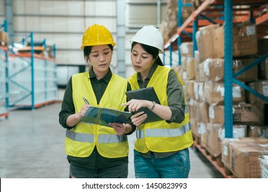 storehouse manager talking with worker in large warehouse. elegant female supervisor teaching new in employee girl while writing on clipboard document. two ladies staff in stockroom wear hard hats.