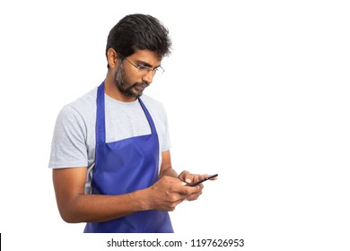 Storekeepeer or indian male employee with eyeglasses using smartphone to text isolated on white studio background