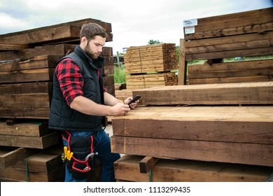 Storesman at small business lumber yard counts stock and records it with his mobile device, phone.