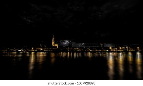 Storm above Antwerp. The night falls in Antwerp and there is a storm coming. Lightning above the cathedral of our Lady. The lights reflect in the Scheldt river.
