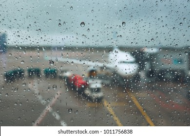Storm at the airport. View of the airplane through rain drops. Themes weather and delay or canceled flight.