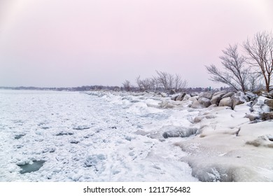 A storm break near Port Dalhousie lighthouse covered in ice and snow on a cold winter day at sunset