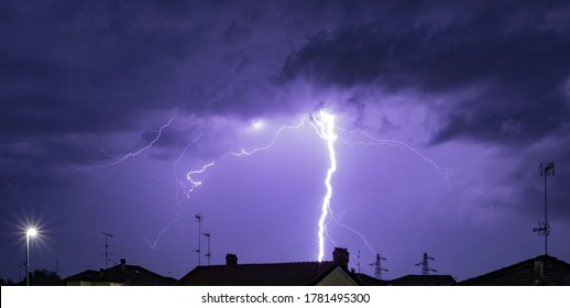 Storm by night over the roofs in Pavia, Italy