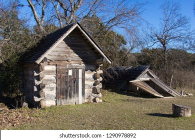 a storm cellar and a log building in a pioneer farm