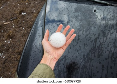 Storm chaser holds a baseball sized hailstone dropped by a supercell thunderstorm.