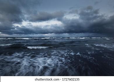 Sturmwolken über der Ostsee im Winter, lange Belastung. Dramatischer Himmel, Wellen und Wasser spritzt. Dunkle Jahreszeit. Deutschland