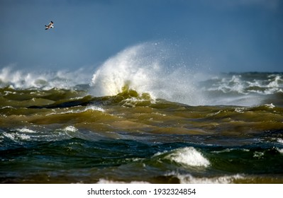 Storm clouds above the Baltic sea in winter. Dramatic sky, waves and water splashes. Dark seascape. Latvia.