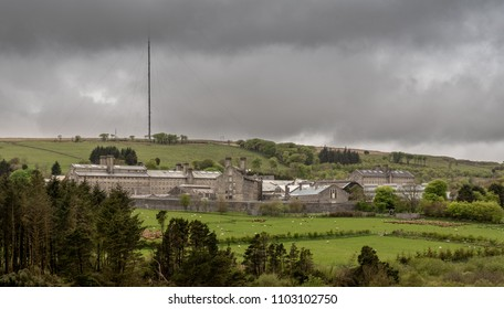 Storm clouds above the granite walls and buildings of HM Prison Dartmoor