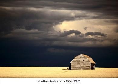 Storm clouds behind abandoned Saskatchewan barn