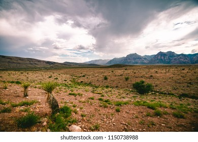 Storm clouds brewing over a vast empty desert in Red Rock Canyon National Park, Las Vegas, Nevada.