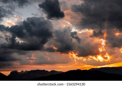 Storm clouds build over a mountain landscape at sunset