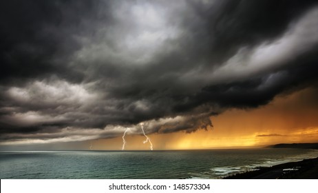 Storm clouds coming over sea with lightning and thunder clouds - dramatic ocean seascape / nature landscape of thunder storm.