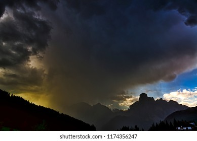 Storm clouds and downpour on the mountains of Alta Badia in summer sunset, Corvara in Badia - Trentino-Alto Adige, Italy