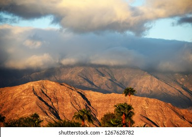 Storm clouds gather above colorful desert mountains with palm trees in foreground.