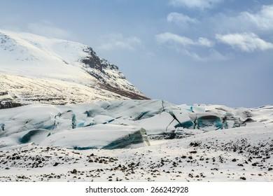 Storm clouds gathering over the fractured blue ice of the Svínafellsjökull Glacier, Iceland