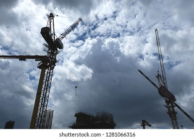 Storm clouds looming over construction cranes - concept for downturn in property market, bleak real estate outlook.