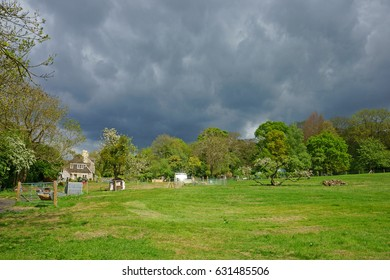 Storm clouds over the Cotswold countryside in Spring with the sun reflected off a glass house, Gloucestershire, England, UK