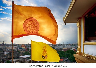 Storm clouds over the Dharmachakra flag, and yellow HM King Bhumibol Adulyadej former king of Thailand flag on the top of the phu khao thong of wat saket, or golden mount. Bangkok, Thailand
