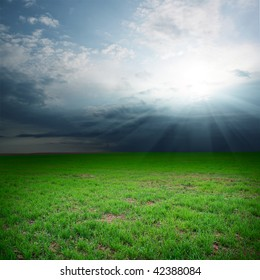 Storm clouds over field with green grass