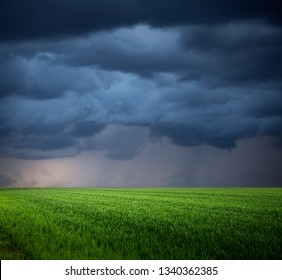 Storm clouds over green field