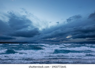 Storm clouds over lake water. Dramatic sky and giant waves.