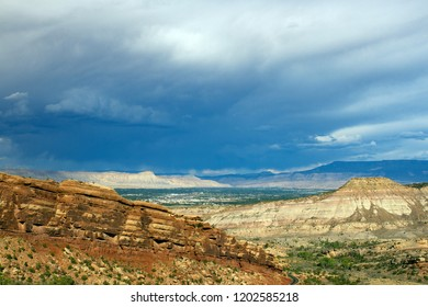 Storm clouds over rocky, sloping bluffs of Colorado National Monument and the city of Grand Junction, Colorado