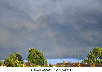 Storm clouds and rainbow over houses