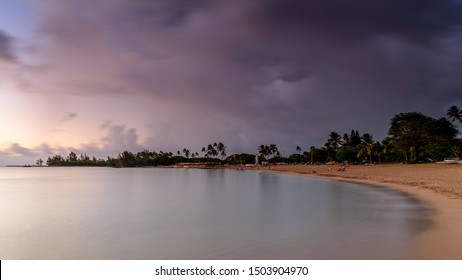 Storm clouds rolling over a tropical beach at sunset. The sea is perfectly calm. The beach is located on the north shore, of Oahu, Hawaii, in the town of Haleiwa