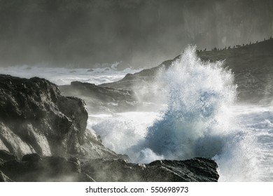 Storm driven, dramatic ocean wave crashes into eroded lava rock creating a tall action splash. Set against dark rocks and substantial ocean spray.